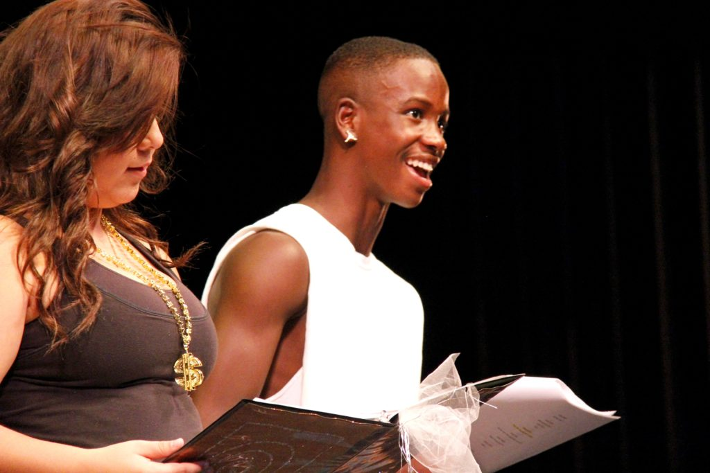 two teens reading from books on stage